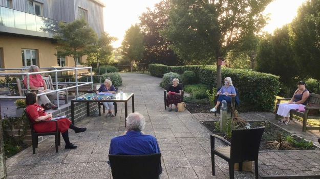 photo of people sitting outside the hospital having a trustee meeting being socially distant